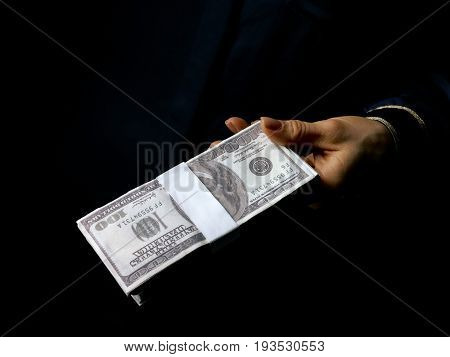 Female Hand Isolated On Black Showing Pack Of Dollars