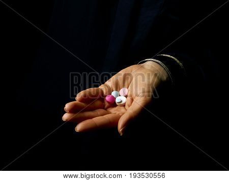 Woman Hand Isolated On Black Showing Pills