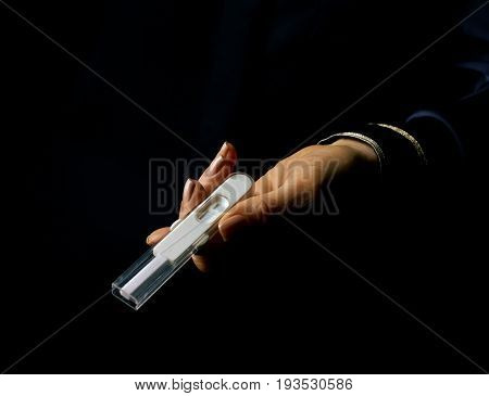 Female Hand Isolated On Black Giving Pregnancy Test