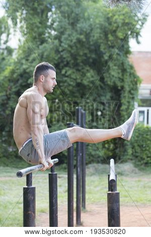 Young Man With A Perfect Body Doing Exercises On The Parallel Bars In The Park