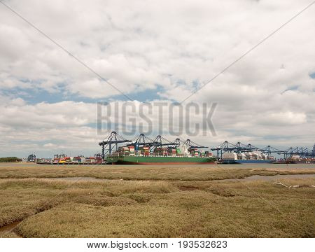 Stock Photo - Blue Sea Structure Cranes At Cargo Dock Loading In Distance Felixstowe Essex
