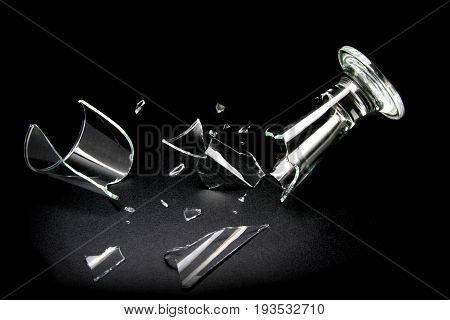 Broken drink glass on black background .