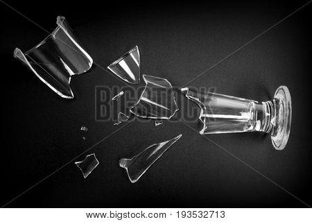 Broken drink glass on black background close up image