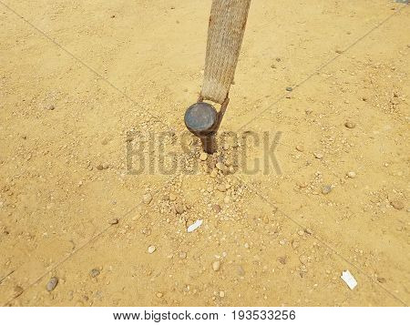metal stake in ground with dirt and many small pebbles
