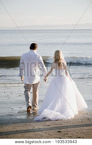Bride and Groom walking into ocean surf.