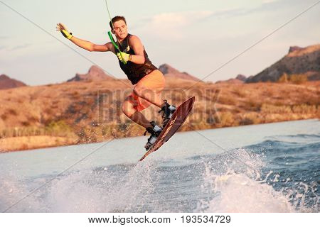 Young man practices the sport of wakeboarding on a placid lake.