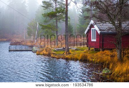 A typical Swedish home located lakeside in a densely misty forest.