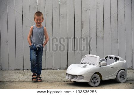 A nice cute dude plays with a toy car on a rural farmstead in a hot summer