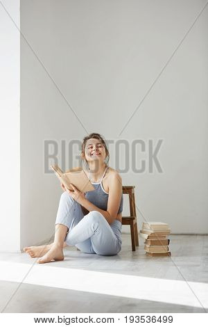 Young beautiful tender girl smiling holding book sitting on floor over white wall early in morning. Copy space.