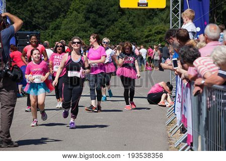 SOUTHAMPTON UK - July 2 2017: Race for Life women run and walk to raise money for Cancer Research charity in Southampton UK. Woman collapsed by finish line due to heat exhaustion lying on ground.