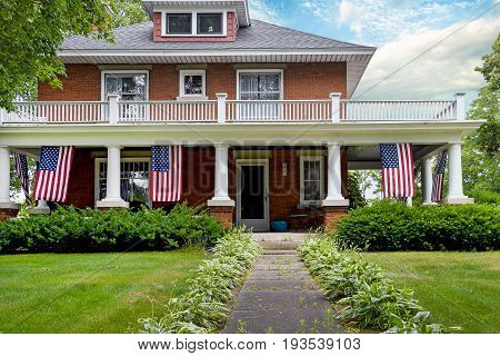 American flag decorations on old brick home with white columns