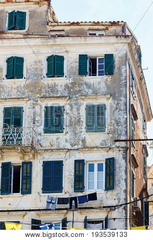 Old building apartments in ramshackle condition. Sky background. Greece, Corfu island