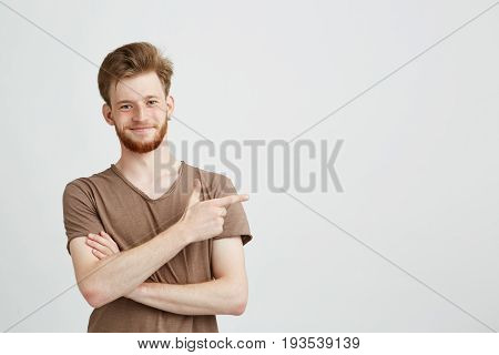 Portrait of young handsome sincere man with beard smiling looking at camera pointing finger in side over white background. Copy space.
