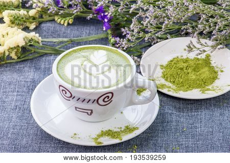 Green tea / Matcha latte in a cup with matcha powder on the wooden table