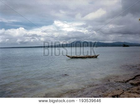 An outrigger canoe sits moored near the shore of the island of Savai'i in Samoa.