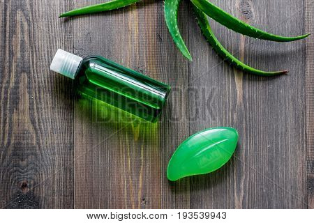 Organic aloe vera cosmetics. Aloe vera leafs, glass of aloe vera juice and soap on wooden table background top view.