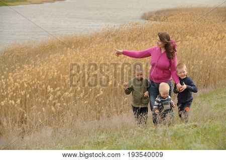 Mother with three sons went for a walk over the lake in the village on a warm May day