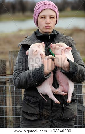 A young girl holds a two pretty piglet in her arms on a rural farmhouse in the early spring on a cloudy day