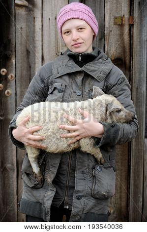 A young girl holds a pretty piglet in her arms on a rural farmhouse in the early spring on a cloudy day