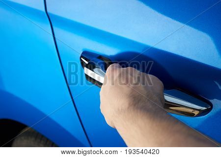 Close-up of opening car door. Hand hold car handle