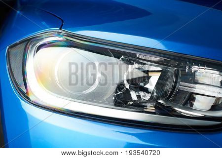 Front car light close-up. Brand new car headlight background