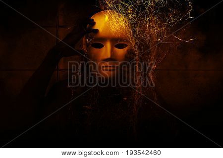 Mysterious woman in black wearing white mask hidden behind spider web,Scary background for book cover