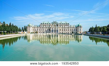 Beautiful view of famous Schloss Belvedere with a reflectant pool and blue sky in Vienna Austria