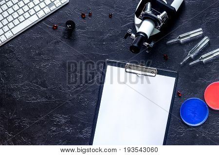 Workplace of doctor. Microscope, ampoule, Petri dish, pad and pills on grey stone background top view.