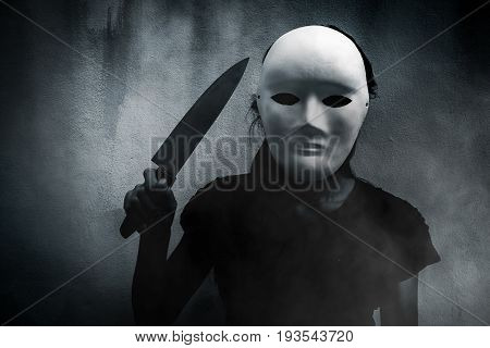 Mysterious woman in black wearing white mask with knife,Scary background for book cover