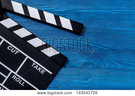 Movie clapperboard on wooden table background top view copyspace.