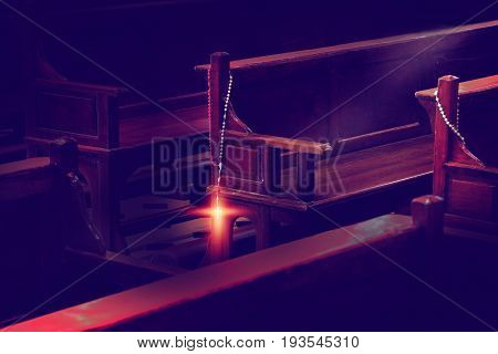 rosary beads Hanging on wooden church pews in dark church