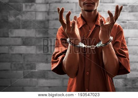 Arrested man in handcuffs on brick wall background