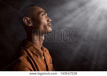 Asian man in prison on smoke background