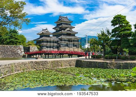Matsumoto Japan - September 6 2016: Matsumoto castle and bright red bridge on sunny day