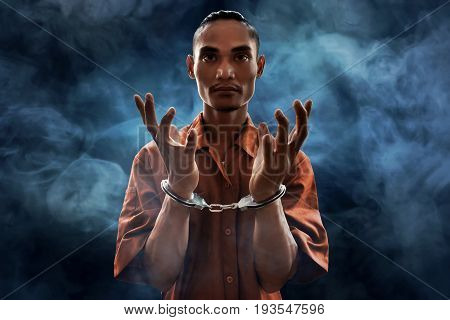 Arrested man in handcuffs on smoke background