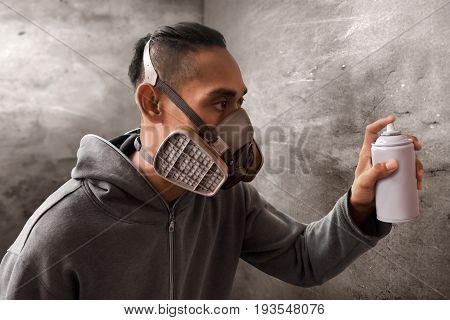 Graffiti artist wearing respirator mask hold spray can