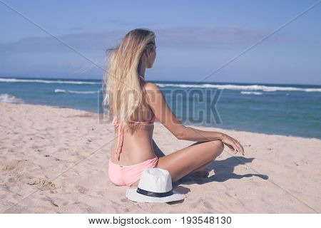 Lonely young sexy woman sitting on the tropical beach by the sea with hat and in the swimsuit. Bali vacation concept.