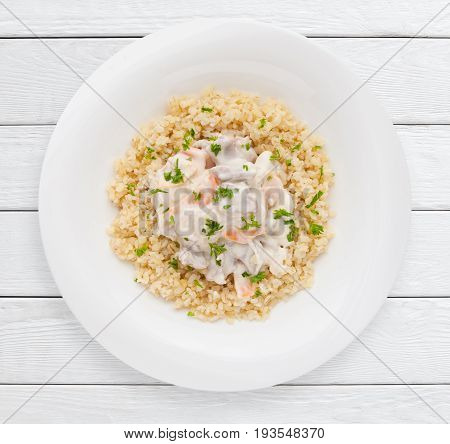 Pearl barley porridge with vegetable sauce top view. Healthy food, sport diet , lunch dish concept. White wooden planks background.