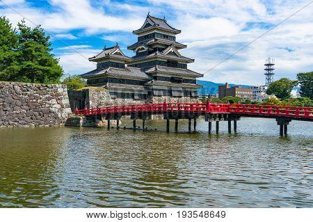Matsumoto Castle And Bright Red Bridge Across Pond