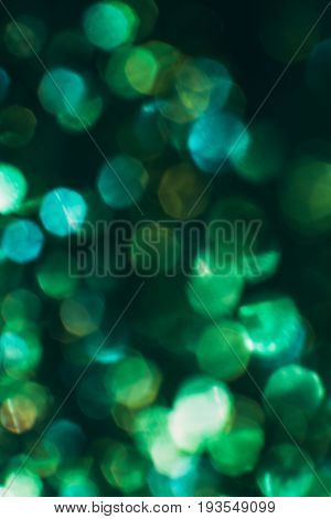 Abstract blurred light background, green halo. Glitter in bokeh. Christmas wallpaper decorations concept. New year holiday festive backdrop. Sparkle circle celebrations display.