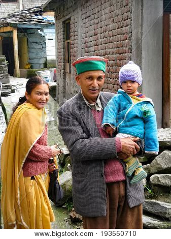 VILLAGE NAGGAR VALLEY KULLU STATE HIMACHAL PRADESH INDIA - APRIL 19 2014: Family with child on the street in small village in Himalayas in north of state Himachal Pradesh.