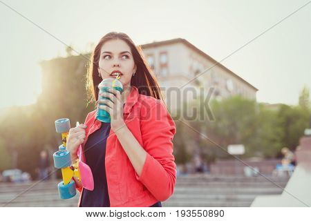 Teen girl holding a glass of fresh fruit. She has a skateboard. Active way of life in urban space. Youth fashion. Close-up portrait