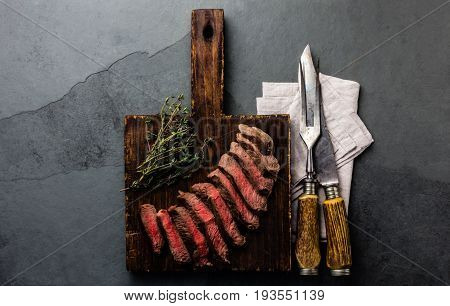 Slices Of Medium Rare Beef Steak On Wooden Board, Vintage Carving Cutlery