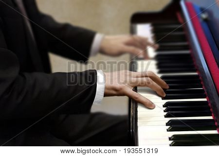 Man in black suit playing piano during concert