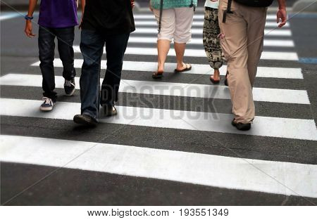 People walking crossing a road during rush hour