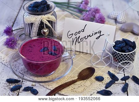 Cup of smoothie, vintage jar with honey berries, cute bicycle, good morning text note and spoon on lace napkin. Morning still life with healthy breakfast, vegetarian and vegan concept