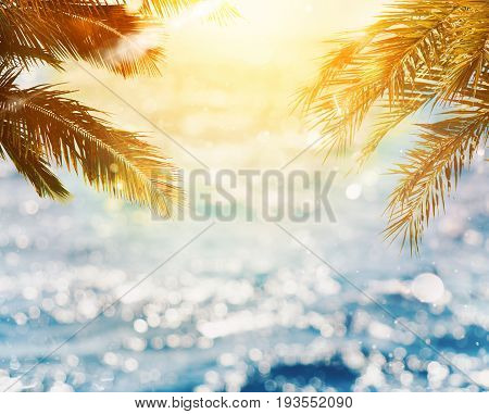 Tropical beach with coconut tree with sunray reflected on the sea on sunset