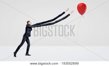 A businessman with extremely long arms trying to catch a red balloon with a gift gold ribbon. Inhuman effort. Striving for success. Get your free gift.