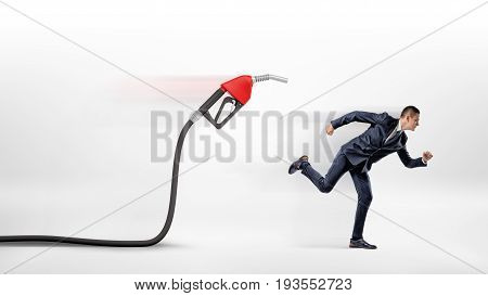 A businessman on white background running away from a red gas nozzle attached to a black hose. Gas station business. Petrol prices. Transportation expenses.