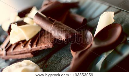 Rich Chocolate dessert photography with chocolate square cookie draped in chocolate and fudge sauce, with white chocolate curls and dark chocolate shavings and chocolate spoons for coffee or dessert conceptual background